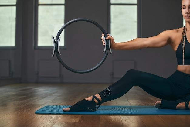Das mädchen trainiert ihre hände mit einem fitness-expander im fitnessstudio, macht liegestütze, trainiert den oberkörper, die schultern, die brust und den trizeps