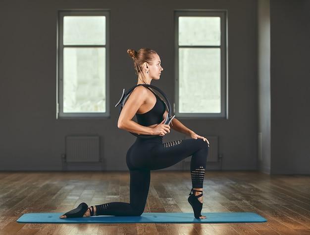 Das mädchen trainiert ihre hände mit einem fitness-expander im fitnessstudio, macht liegestütze, trainiert den oberkörper, die schultern, die brust und die trizeps-fitness-motivation