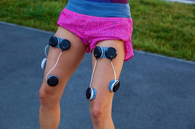 Das mädchen trainiert mit einem elektrostimulator. übungen und belastung der beinmuskulatur mit einem elektrostimulator.