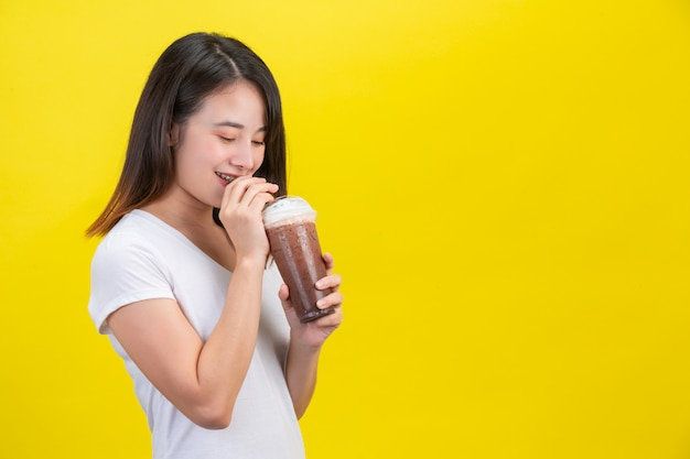 Das mädchen trinkt kaltes wasser aus kakao aus einem durchsichtigen plastikglas auf gelbem grund.