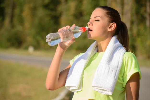 Das mädchen trinkt morgens nach dem joggen wasser.