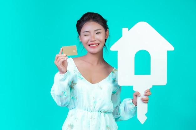 Das mädchen trug ein weißes langarmhemd mit blumenmuster, das ein weißes haussymbol und eine goldene kreditkarte mit einem blauen schriftzug enthielt.