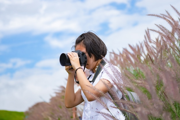 Das mädchen übt berufsphotographie beim reisen auf einer schönen wiese.