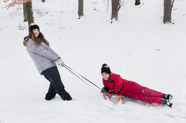 Das mädchen und der junge, die spaßschlitten haben, fahren auf schneebedeckte landschaft