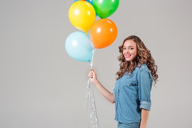 Das mädchen und ein haufen bunter luftballons an der grauen wand