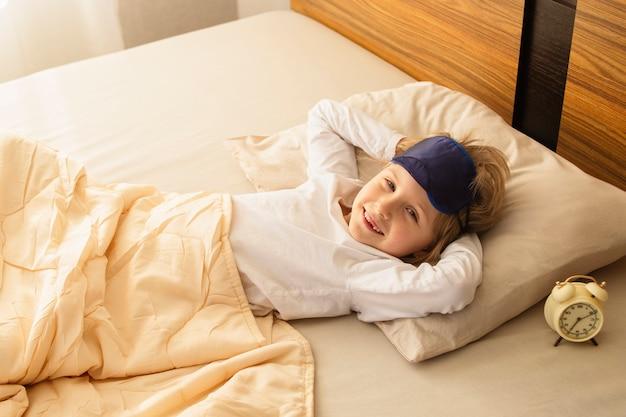 Das mädchen wachte leicht auf und stand morgens gut gelaunt auf. das mädchen lächelt und hat gut geschlafen. guten morgen, wecker.