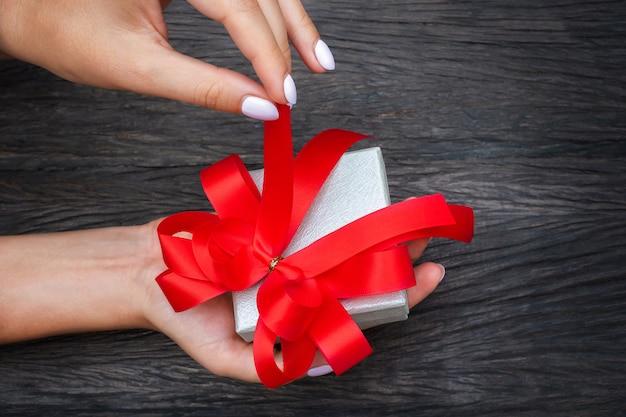 Das mädchen wird die rote schleife an der geschenkbox an der hand lösen.