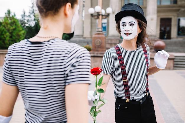 Das männliche pantomimegeschenk stieg zum weiblichen pantomimen
