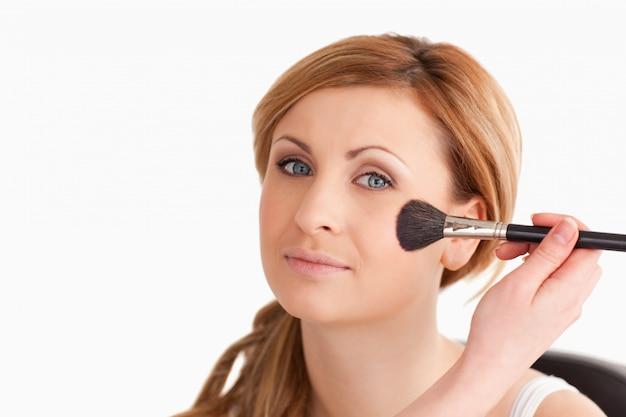 Das make-upkünstleranwenden bilden zu einer attraktiven blonden frau