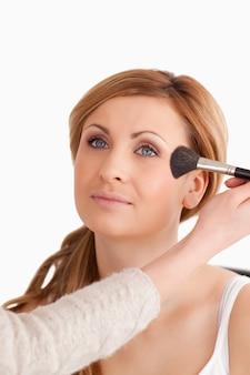 Das make-upkünstleranwenden bilden zu einer attraktiven frau