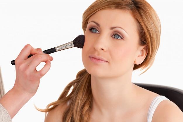 Das make-upkünstleranwenden bilden zu einer netten blond-haarigen frau