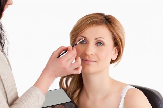 Das make-upkünstleranwenden bilden zu einer netten frau