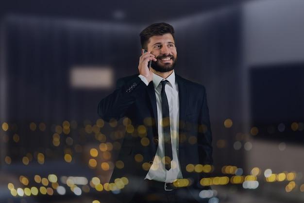Das manntelefon am fenster mit stadtlichtern