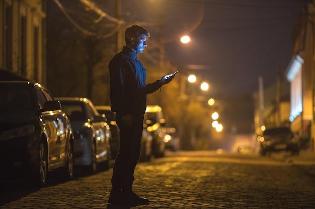 Das manntelefon auf der straße. abend nachtzeit. aufnahme mit teleobjektiv