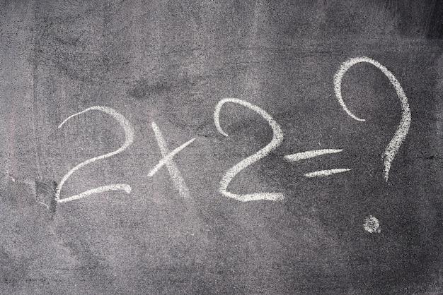 Das mathematische beispiel zwei mal zwei ist in weißer kreide auf schwarzer kreidetafel geschrieben