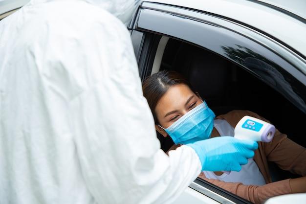 Das medizinische team des ppe-personals überprüft die temperatur, um das coronavirus des patienten im auto zu überprüfen