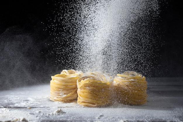Das mehl wird durch ein sieb auf rohen tagliatelle-nudeln auf einem hölzernen küchentisch gesiebt.