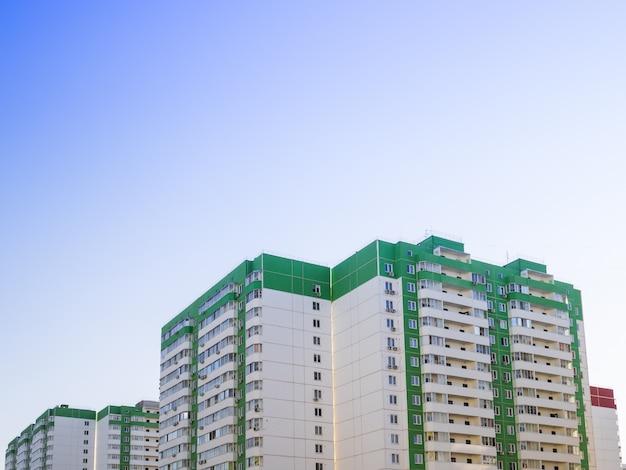 Das mehrstöckige haus ist grün vor einem klaren blauen himmel