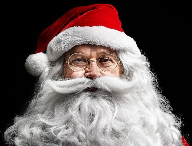 Das menschliche gesicht des weihnachtsmanns auf der schwarzen wand