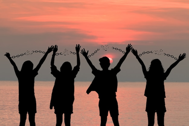 Das menschliche schattenbild der gruppe der menschlichen handkette fehlt, erhalten freiheit, über sonnenuntergangshimmel