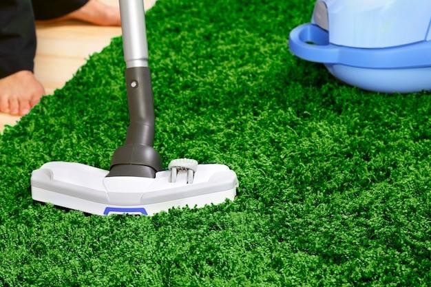 Das metallrohr des staubsaugers in aktion - reinigen sie einen teppich und eine laminatbodenplatte.