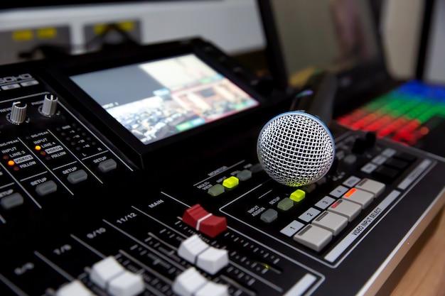 Das mikrofon wird im studio auf den professionellen audiomixer gestellt.
