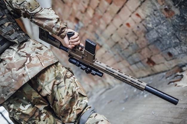 Das militär hält einen helm und ein gewehr in den händen.