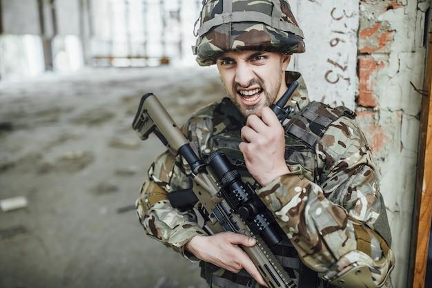 Das militär spricht vernünftig und hält ein großes gewehr