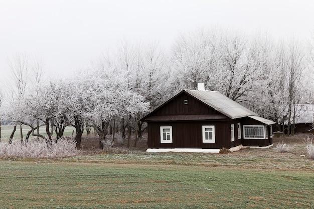 Das mit schnee bedeckte landhaus im winter befindet sich auf einem bauernhof