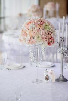 Das mittelstück, das von den rosa und weißen blumen gemacht wird, steht mitten in festlichem abendtisch