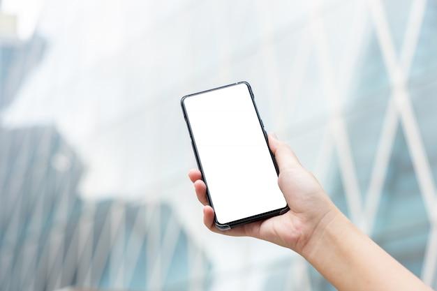 Das modellbild der frauenhand mobile smartphones halten lokalisierte weißen bildschirm