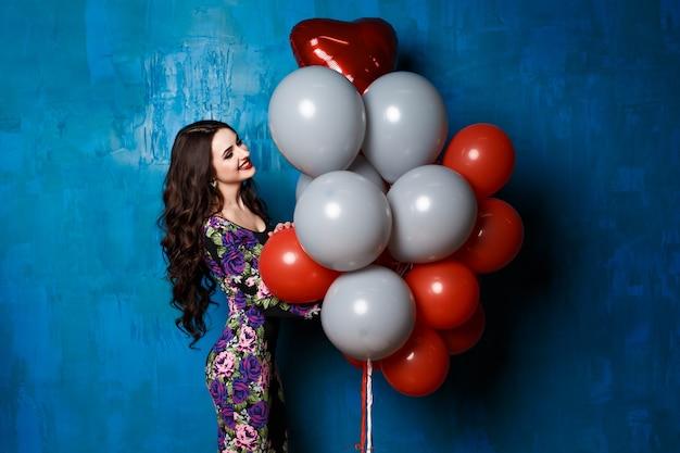 Das modeporträt der glamour lady mit perfektem make-up und strahlender haut, vollen roten lippen und großen augen hält luftrote und weiße luftballons. sexy perfekte passform körper frau. attraktive sexy und junges mädchen