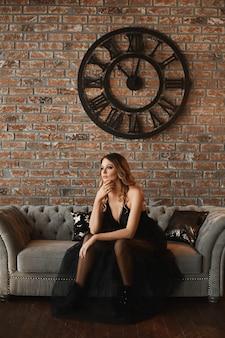 Das modeporträt eines jungen schönen weiblichen modells im lässigen schwarzen kleid und in den schwarzen stiefeln sitzt auf dem vintage-sofa