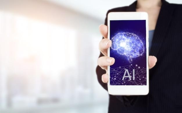 Das moderne konzept des cyberhirns. hand halten weißes smartphone mit digitalem hologramm künstliche gehirnintelligenz-zeichen auf leicht unscharfem hintergrund. künstliche intelligenz ki.