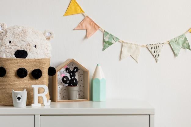 Das moderne skandinavische neugeborene babyzimmer mit kopierraum, holzauto, plüschspielzeug und wolken. hängende baumwollfahnen und weiße sterne. minimalistisches und gemütliches interieur mit weißen wänden.