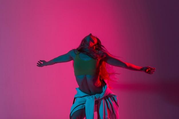 Das modische modemodell der hübschen jungen frau in sportbekleidung genießt einen tanz in einem raum mit mehrfarbigem licht. stilvolles schönes sexy mädchen, das drinnen mit leuchtend rosa neon flackert.