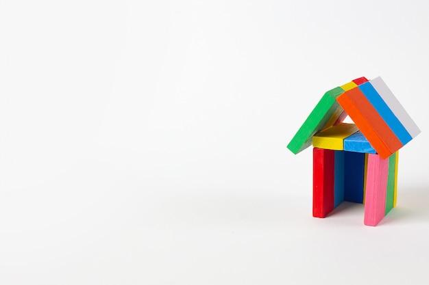 Das multi farbaufbautenhaus des dominos auf weißem hintergrund.