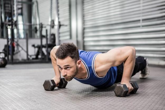 Das muskulöse mannhandeln drückt mit dummköpfen an der crossfit turnhalle hoch