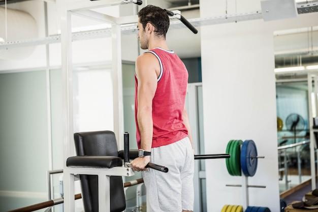 Das muskulöse mannhandeln zieht in einer turnhalle hoch