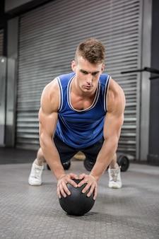 Das muskulöse mannhandeln zieht mit medizinball an der crossfit turnhalle hoch