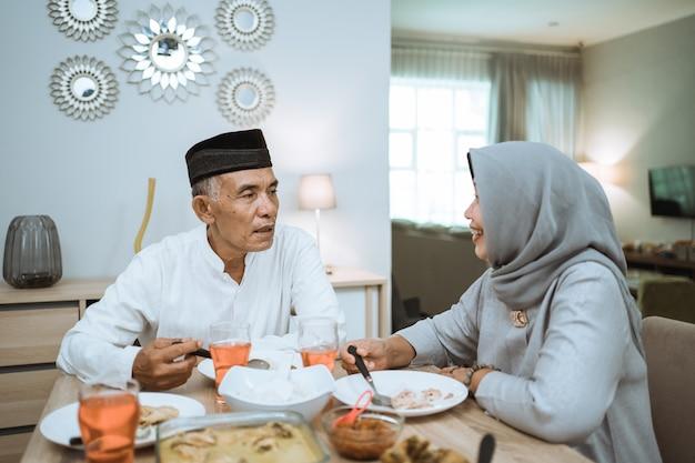 Das muslimische seniorenpaar genießt sein gemeinsames iftar-abendessen zu hause