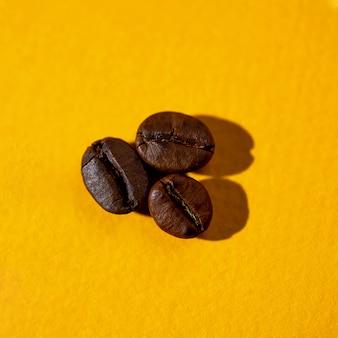 Das muster der kaffeebohnen auf farbiger oberfläche
