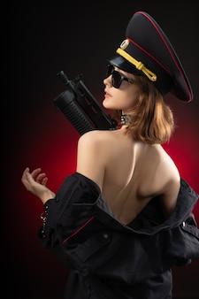 Das nackte mädchen in polizeiuniform mit einer waffe. englische übersetzung der polizei