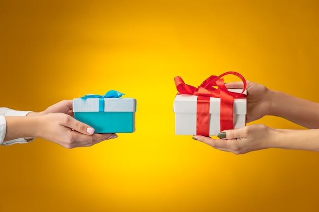 Das nahaufnahmebild der hände von mann und frau mit geschenkbox auf gelbem hintergrund
