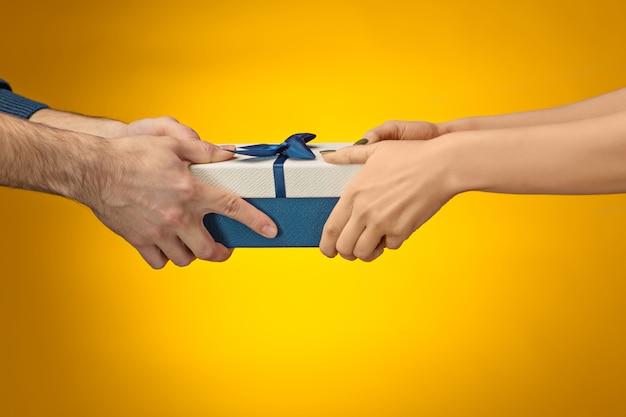 Das nahaufnahmebild der hände von mann und frau mit geschenkbox