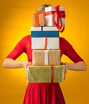Das nahaufnahmebild von frauenhänden mit geschenkboxen auf gelbem hintergrund