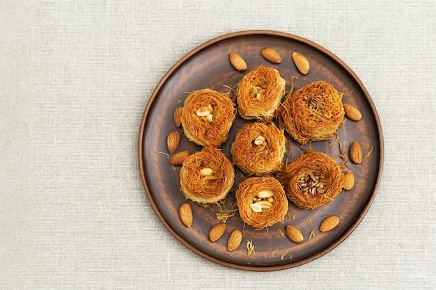 Das nest des traditionellen nahöstlichen süßen vogels mit sirup des honigs und der nüsse auf platte auf textiltischdecke. köstlicher honignachtisch vom dünnen teig phylo. ansicht von oben.