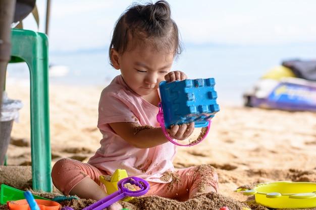 Das nette asiatische baby, das mit strand spielt, spielt auf dem strand