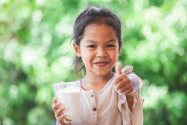 Das nette asiatische kindermädchen, das glas milch hält und machen starke geste