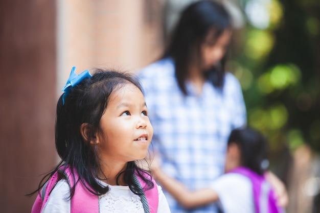 Das nette asiatische kindermädchen, das ihre schwester wartet, gehen zur schule zusammen, nachdem sie ihre mutter umarmt hat
